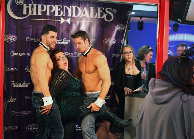 A woman poses with Chippendale dancers during New Year's Eve festivities at the Fremont Street Experience in downtown Las Vegas Tuesday, Dec. 31, 2013. An estimated 335,000 tourists were expected to visit Las Vegas to celebrate the new year.