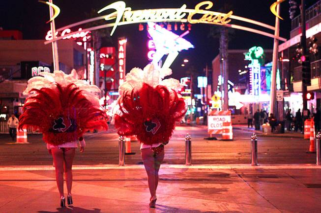 Showgirl street performers are shown during New Year's Eve festivities in downtown Las Vegas Tuesday, Dec. 31, 2013. An estimated 335,000 tourists were expected to visit Las Vegas to celebrate the new year.