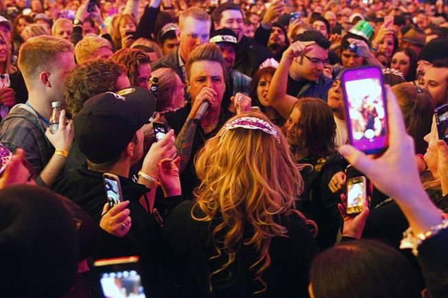 Coby, lead singer of Papa Roach, goes into the crowd during their set at the Fremont Street Experience in downtown Las Vegas, Tuesday Dec. 31, 2013. An estimated 335,000 tourists were expected to visit Las Vegas to celebrate the new year.