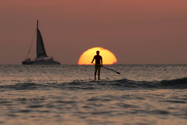 A paddle boarder looks out over the Pacific Ocean as the sun sets off Waikiki Beach, in Honolulu, on Tuesday, Dec. 31, 2013.