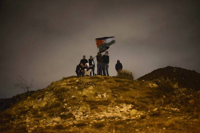 Palestinians wave their national flag as they await the release of Palestinian prisoners in Jerusalem, Tuesday, Dec. 31, 2013. Israel released more than two dozen Palestinian prisoners convicted in deadly attacks against Israelis early Tuesday as part of a U.S.-brokered package to restart Mideast peace talks.