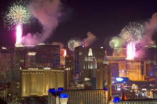 Fireworks fired from casino rooftops explode over the Las Vegas Strip just after midnight Jan. 1, 2014. An estimated 335,000 tourists were expected to visit Las Vegas for the New Year's festivities. Photo taken from the Mix nightclub at Mandalay Bay.