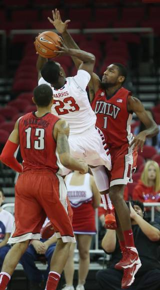 Fresno State's Marvelle Harris finds little room to shoot against UNLV's Roscoe Smith (1) in the first half of a NCAA college basketball game in Fresno, Calif., Wednesday, Jan. 1, 2014.