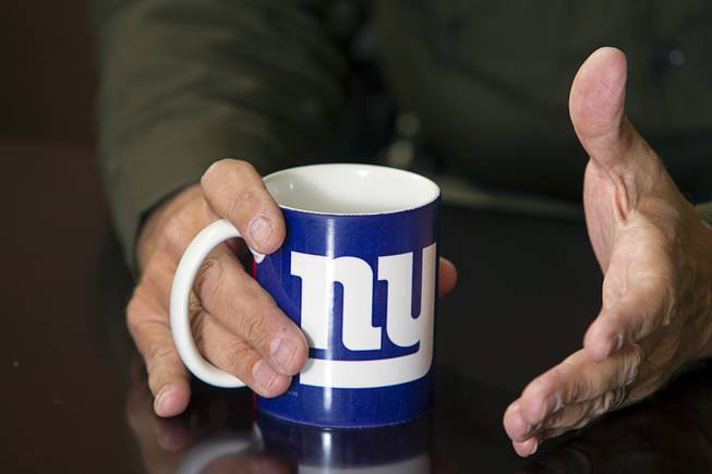 Sheriff Doug Gillespie, originally from a small town in upstate New York, holds a mug with a New York Giants logo during an interview at his office in Metro Police Headquarters Thursday, Jan. 2, 2014.