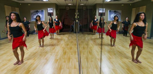 A hula workout class at the Self Quest Institute Dance Studio is reflected in a mirror on Friday, Jan. 3, 2014.