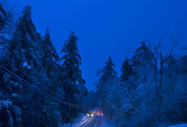 Utility crews prepare to work on power lines at dusk, Thursday, Dec. 26, 2013, in Litchfield, Maine, where many have been without electricity since Monday's ice storm.  Up to 7 inches of snow is forecast, worrying utilities that the additional weight on branches and transmission lines could cause setbacks in the around-the-clock efforts to restore power.