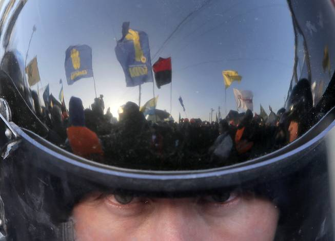 A thousand-strong pro-European Union rally is reflected in the surface of a riot police officer's helmet as he guards the way to Ukrainian President Viktor Yanukovychs country residence of Mezhygirya outside Kiev, Ukraine, Sunday, Dec. 29, 2013. Hundreds of riot police blocked approaches to Mezhygirya as protesters demanded Yanukovych's resignation over his decision to ditch a pact with the European Union in favor of closer ties with Russia.