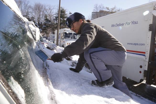 US Postal Service letter carrier Danny Kim clears snow and ice as he climbs on the hood of his mail delivery truck in the parking lot at the U.S. Post Office in Bethesda, Md., Friday, Jan. 3, 2014. Kim said that despite the storm resulting in many closing of local school systems, he and his colleagues were working on an unchanged schedule. A winter storm that swept across the Midwest this week blew through the Northeast and its biggest cities on Friday, producing more than a foot of snow in spots, giving rise to wind gusts that threatened trees and power lines, and leaving bone-chilling cold in its wake. (AP Photo/Charles Dharapak)