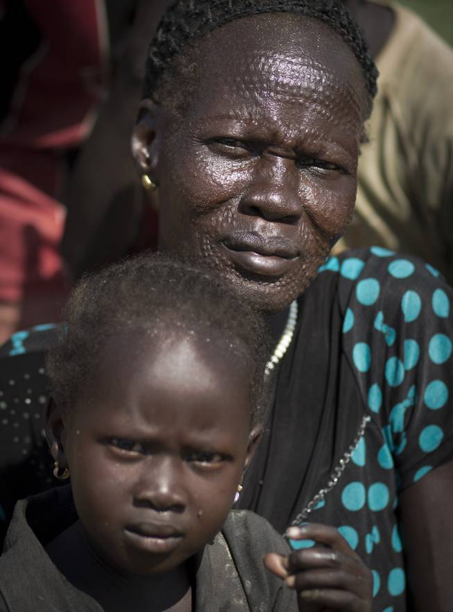 "A displaced woman showing traditional scarification on her face sits with a child inside a United Nations compound which has become home to thousands of people displaced by the recent fighting, in Juba, South Sudan Friday, Dec. 27, 2013. Kenya's president Uhuru Kenyatta on Friday urged South Sudan's leaders to resolve their political differences peacefully and to stop the violence that has displaced more than 120,000 people in the world's newest country, citing the example of the late Nelson Mandela and saying there is ""a very small window of opportunity to secure peace"" in the country where fighting since Dec. 15 has raised fears of full-blown civil war."