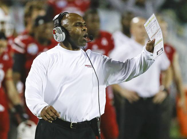 Louisville coach Charlie Strong calls out to players on the field during the second half of the Russell Athletic Bowl NCAA college football game against Miami in Orlando, Fla., Saturday, Dec. 28, 2013.
