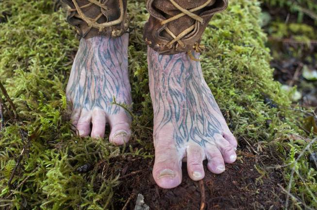 "Mick Dodge's feet are tattooed with the images of roots. He stands on some moss at his cabin along the Sol Duc River near Forks, Wash., on January 3, 2014. Dodge is the subject of ""The Legend of Mick Dodge"" on the National Geographic Channel."