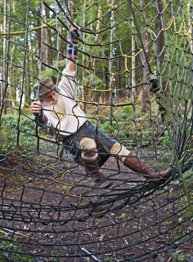 Mick Dodge climbs a cargo net at his cabin along the Sol Duc River near Forks, Wash., on January 3, 2014.
