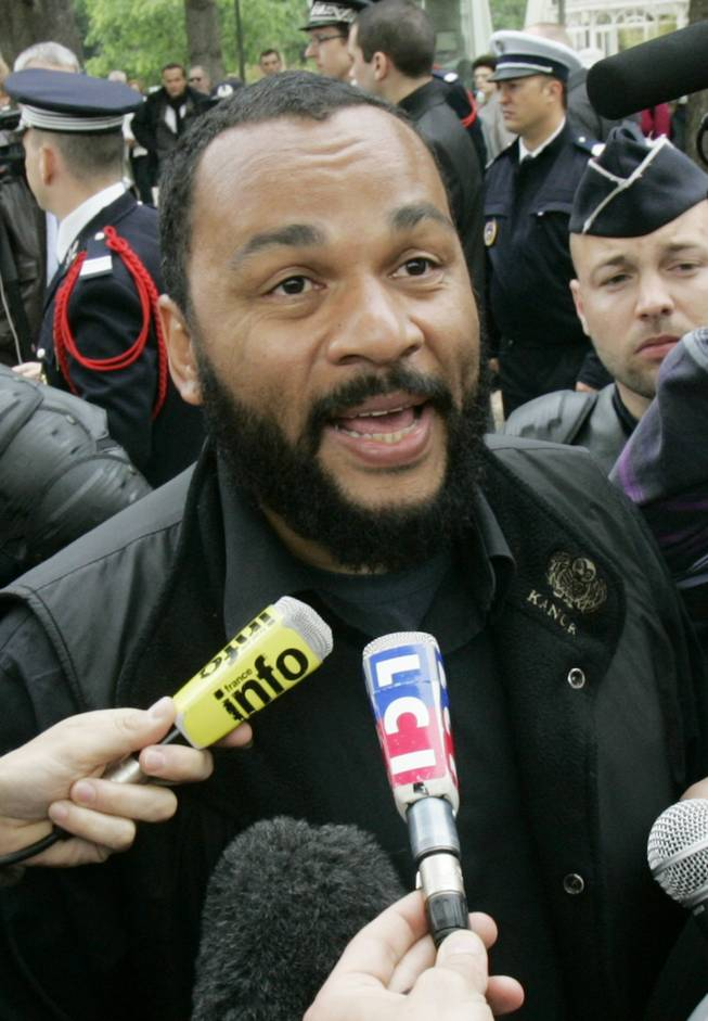 In this May 13, 2009, file photo, controversial French comic Dieudonne M'Bala M'Bala, known as Dieudonne, answers reporters as he heads for the interior Ministry to submit a list of candidates for the upcoming European elections, in Paris. The Paris prosecutor's office said Thursday Jan. 2, 2013, it is investigating threats against a comedian the French interior minister wants banned from the stage for what he says are racist and anti-Semitic performances.