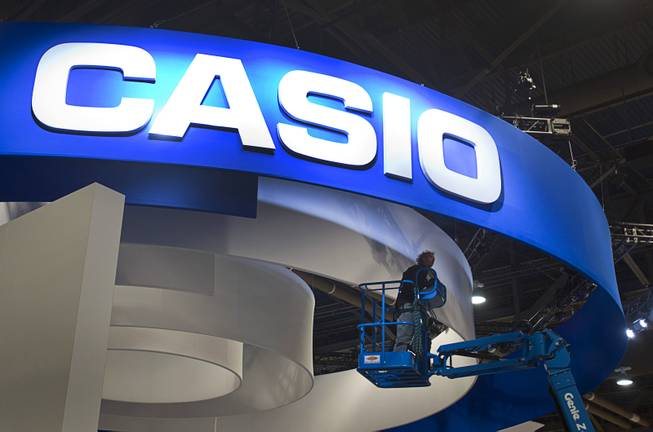 A worker checks on lights at a Casio booth during set up  for the 2014 Consumer Electronics Show (CES) at the Las Vegas Convention Center Saturday, Jan. 4, 2014.