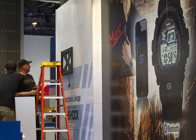 Workers set up a display at a Casio booth in preparation for the 2014 Consumer Electronics Show (CES) at the Las Vegas Convention Center Saturday, Jan. 4, 2014.