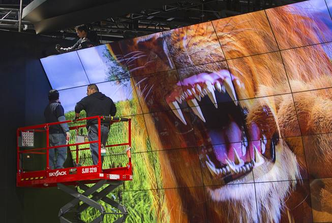 Technicians work on a LG Electronics 3-D video wall in preparation for the 2014 Consumer Electronics Show (CES) at the Las Vegas Convention Center Saturday, Jan. 4, 2014.