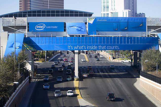 Traffic passes under a monorail station covered with an Intel wrap for the 2014 Consumer Electronics Show (CES) near the Las Vegas Convention Center Saturday, Jan. 4, 2014.