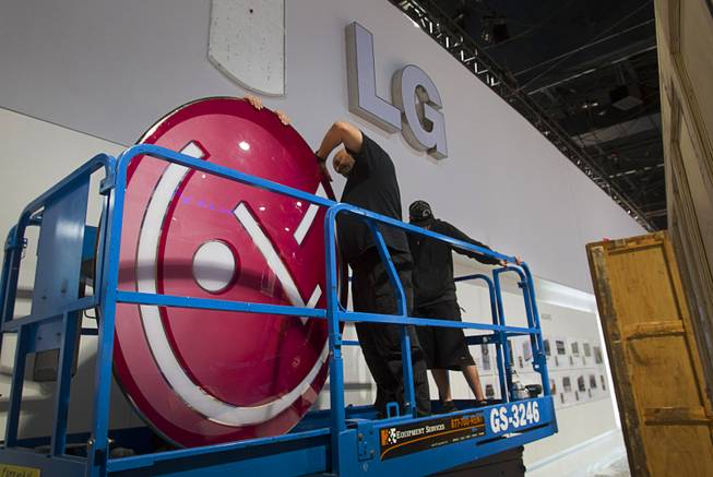 Workers prepare to hang the LG Electronics logo as they build a booth in preparation for the 2014 Consumer Electronics Show (CES) at the Las Vegas Convention Center Saturday, Jan. 4, 2014.