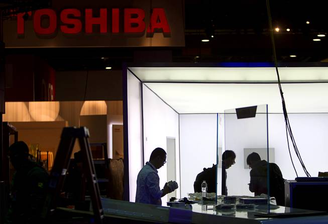 Technicians with TCL Communication put together a display near the Toshiba booth in preparation for the 2014 Consumer Electronics Show (CES) at the Las Vegas Convention Center Saturday, Jan. 4, 2014.