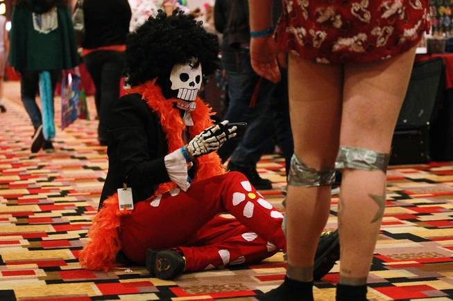 Jacob van Patten sits on the ground while looking at his phone at Otakon Vegas on Saturday, Jan. 4, 2014, at Planet Hollywood.