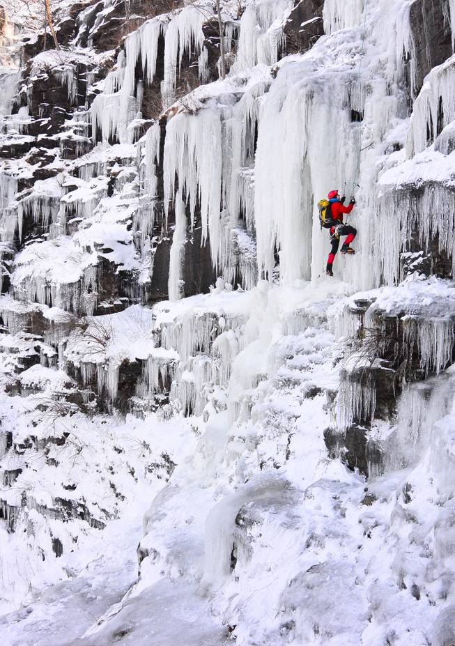 Ice climber Howie Mievogel uses ice tools and crampons to ascend a frozen waterfall on the cliffs in Riegelsville, Pa. near the Delaware River,  Saturday, Jan. 4, 2014. Below zero temperatures have brought ice climbers out of hiding the past few days.