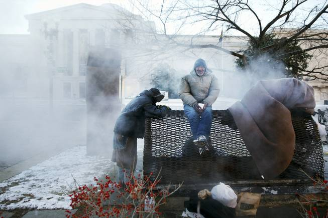 Four homeless men warm themselves on a steam grate by the Federal Trade Commission, blocks from the Capitol, during frigid temperatures in Washington on Saturday, Jan. 4, 2014.