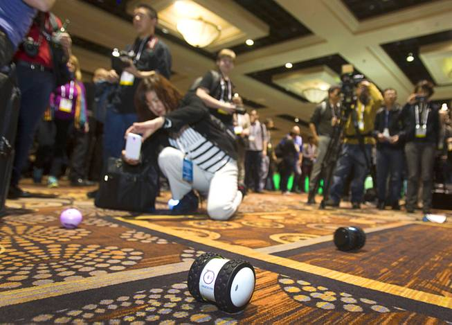 "A woman takes a photo of a Sphero 2.0 by Orbotix during ""CES Unveiled,"" a media preview event to the annual Consumer Electronics Show (CES), in Las Vegas, Jan. 5, 2014. The Sphero 2.0 and 2B (foreground) are controlled with a smartphone. The Sphero 2.0 is already available. The 2B expected to ship in the fall of 2014, a representative said."
