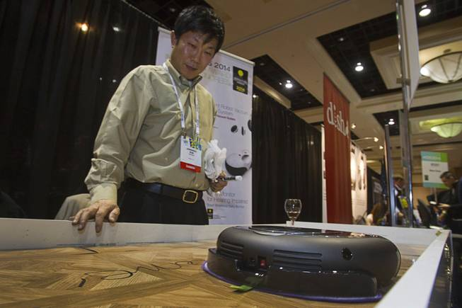 "Jong Soo Kim gives a demonstration of Moneual's Rydis H68 Pro Hybrid Robot Vacuum during ""CES Unveiled,"" a media preview event to the annual Consumer Electronics Show (CES), in Las Vegas, Jan. 5, 2014. The robot can vacuum, wet-mop floors and uses smart vision technology to map out floor plans."