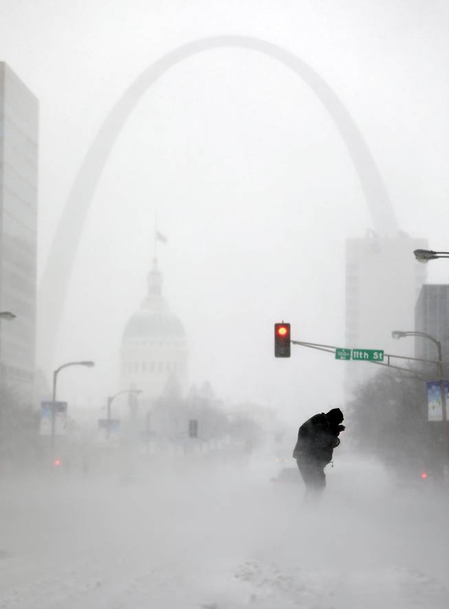 A person struggles to cross a street in blowing and falling snow as the Gateway Arch appears in the distance Sunday, Jan. 5, 2014, in St. Louis. Snow that began in parts of Missouri Saturday night picked up intensity after dawn Sunday with several inches of snow on the ground by midmorning and more on the way.