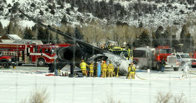 Emergency crews work near a passenger plane that crashed upon landing at the Aspen-Pitkin County Airport in Aspen, Colo., Sunday, Jan. 5, 2014.