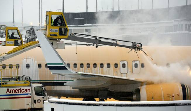 Crews work to de-ice planes at O'Hare International Airport in Chicago on Sunday, Jan. 5, 2014. Temperatures not seen in years are likely to set records in the coming days across the Midwest, Northeast and South, creating dangerous travel conditions and prompting church and school closures.