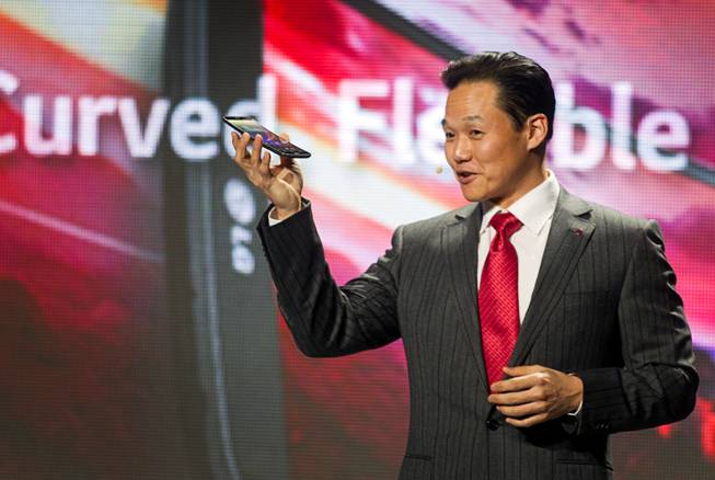 Frank Lee, head of mobile communications for LG Electronics USA, holds a curved G Flex smartphone by LG  during the 2014 International Consumer Electronics Show (CES) in Las Vegas, Monday Jan. 6, 2014.