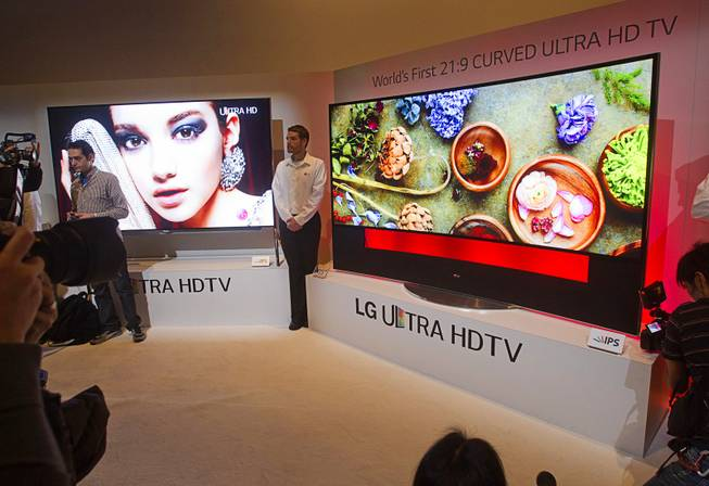 Journalists get an early look at a curved OLED Ultra HD television by LG Electronics during the 2014 International Consumer Electronics Show (CES) in Las Vegas, Monday Jan. 6, 2014.