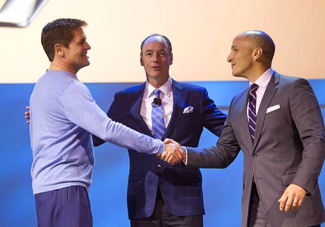 Entrepreneur Mark Cuban (L) shakes hands with Pete Bevacqua, CEO of the Professional Golf Association of America as Tim Baxter (C), president of Samsung Electronics America looks on during the International Consumer Electronics Show (CES), in Las Vegas, Monday Jan. 6, 2014.