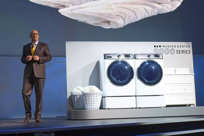 Kevin Dexter, senior vice president of Samsung Electronics America, shows off the 9000 Series clothes washer and dryer during the International Consumer Electronics Show (CES), in Las Vegas, Monday Jan. 6, 2014. The 9000 Series is the world's largest washer and dryer, Dexter said.