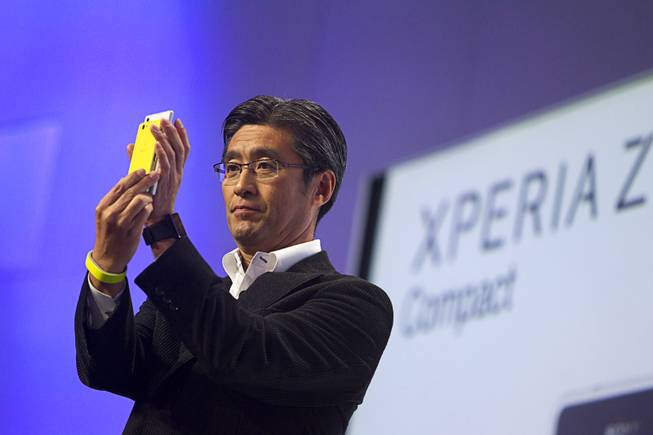Kunimasa Suzuki, president/CEO of Sony Mobile Communications,  compares the size of an Experia Z1 Smartphone with a new smaller Xperia Z1 Compact during a Sony news conference at the International Consumer Electronics Show (CES), in Las Vegas, Monday Jan. 6, 2014.