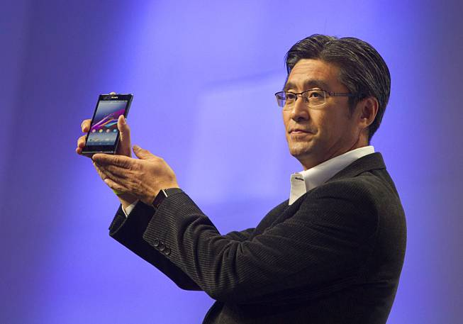 Kunimasa Suzuki, president/CEO of Sony Mobile Communications, displays a Sony XperiaZ1s smartphone during a Sony news conference at the International Consumer Electronics Show (CES), in Las Vegas, Monday Jan. 6, 2014. The Xperia Z1s will be available exclusively through T Mobile and be available nationwide on january 22, he said.