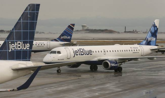 A JetBlue airplane taxis to park at a gate at Logan Airport, Monday, Jan. 6, 2014, in Boston. JetBlue announced that they would halt operations in Boston, New York and New Jersey later in the afternoon, to rest their crews and give it time to service aircraft, due to flight delays and cancellations. Heavy rains in the East, and sub-zero temperatures in the Midwest, threw airlines and travel plans into havoc.