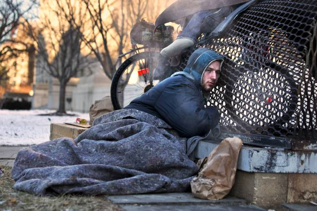 Nick warms himself on a steam grate with three other homeless men by the Federal Trade Commission, just blocks from the Capitol, during frigid temperatures in Washington, Saturday, Jan. 4, 2014. A winter storm that swept across the Midwest this week blew through the Northeast on Friday, leaving bone-chilling cold in its wake.