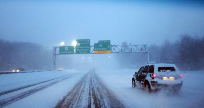 "Motorists navigate northbound U.S. 31 near the I-96 exit in blowing snow and sub-zero conditions Monday morning, Jan. 6, 2014, near Norton Shores, Mich. A whirlpool of frigid, dense air known as a ""polar vortex"" descended Monday into much of the U.S."
