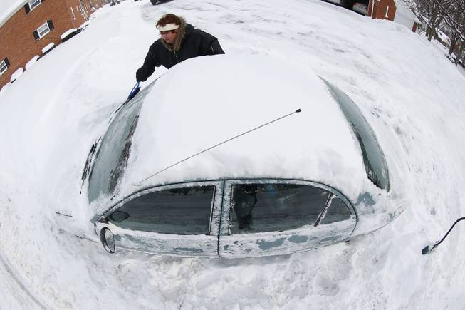 In an imagge made with a fisheye lens, Marguerite Johnston uncovers her car in Grosse Pointe, Mich., Monday, Jan. 6, 2014. Michigan residents are preparing for diving temperatures as they dig out from more than 15 inches of snow in places.
