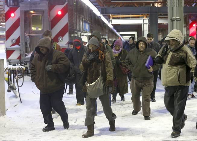 Commuters arrive at the La Salle Street commuter rail station as they experience temperatures well below zero and wind chills expected to reach 40 to 50 below, Monday, Jan. 6, 2014, in Chicago.