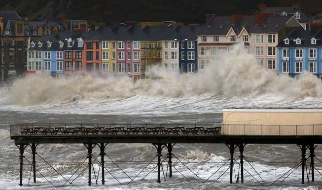 Waves crash against the promenade in Aberystwyth, Wales  Monday Jan. 6, 2014  as strong winds and high tides continue in western Britain.