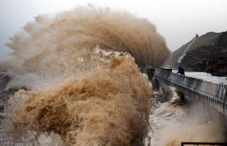 Waves crash onto the promenade between Fleetwood and Blackpool, as high tides and huge waves hit the North West England, Monday Jan. 6, 2014.