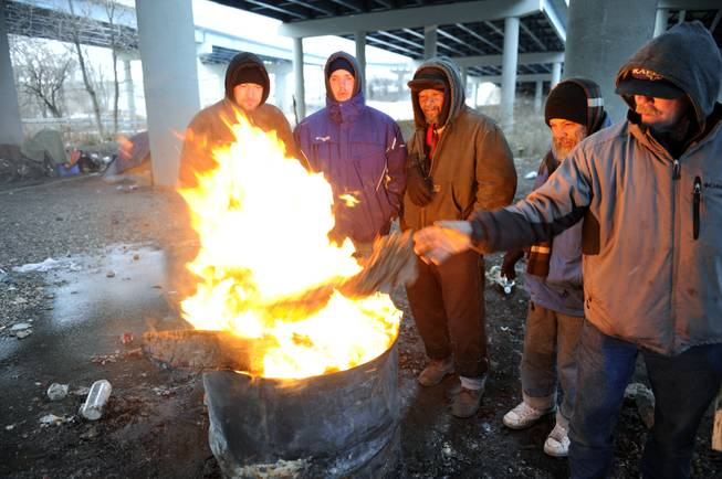 Michael Best, right, and others who identified themselves as homeless use donated wood and a fire barrel to keep warm Monday, Jan. 6, 2014, in Knoxville, Tenn. Monday's expected high temperature in Knoxville of around 24 degrees came hours before dawn, and is expected to fall into the single digits for most of East Tennessee.
