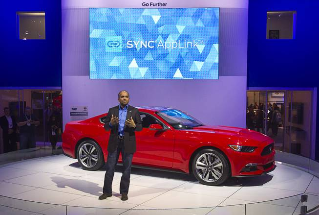 Raj Nair, Ford Motor Company's group vice president of global product development,  speaks in front of a 2015 Ford Mustang during the 2014 International Consumer Electronics Show (CES) at Las Vegas Convention Center in Las Vegas, Tuesday Jan. 7, 2014. The new Mustang will be the first model in North America to feature the enhanced Ford SYNC AppLink system. The improvements include better voice control and simpler menus, a representative said.