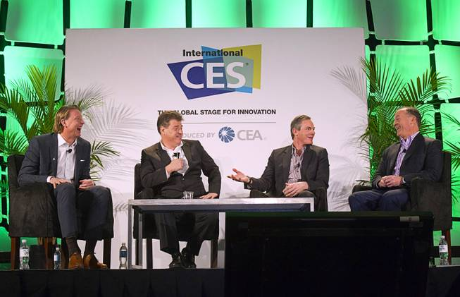 "Panelists (L-R) Hans Vestberg, president/CEO of Ericsson Group, moderator Andrew Keen, Paul Jacobs, chairman and CEO of Qualcomm, and John Donovan, senior vice president of technology and network operations for AT&T, prepare for a discussion on the ""Global Innovation of Mobile"" at the 2014 International Consumer Electronics Show (CES) in Las Vegas, Tuesday Jan. 7, 2014."