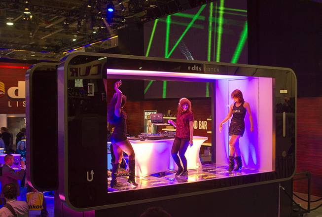 Dancers and a DJ perform in a stage shaped like a giant smarphone at the DTS booth during the 2014 International Consumer Electronics Show (CES) in Las Vegas, Tuesday Jan. 7, 2014.