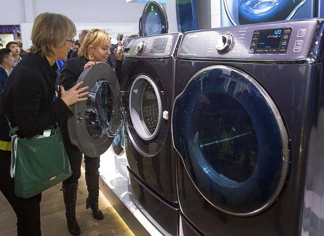 Kate Bulkley (L) and Susan Brazer look over the Samsung Electronics 9000 Series washer and dryer during the 2014 International Consumer Electronics Show (CES) in Las Vegas, Tuesday Jan. 7, 2014. The washer and dryer are the world's largest Samsung says.