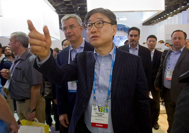 Yoon Boo-Keun, center, Co-Chief Executive Officer at Samsung Electronics, gives retailers a tour of the Samsung booth at Samsung Electronics  during the 2014 International Consumer Electronics Show (CES) in Las Vegas, Tuesday Jan. 7, 2014.